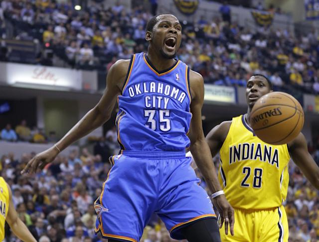 Oklahoma City Thunder forward Kevin Durant reacts after a dunk in front of Indiana Pacers center Ian Mahinmi in the first half of an NBA basketball game in Indianapolis, Sunday, April 13, 2014. (AP Photo/Michael Conroy)