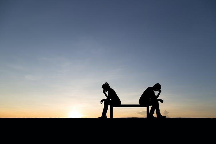 Two people sitting on a bench, with sunset in the background, with their heads in their hands.