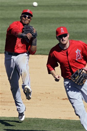 Los Angeles Angels shortstop Erick Aybar, left, makes a late throw over third baseman Mark Trumbo in attempt to out Chicago White Sox's Brent Lillibridge at first on an infield single during the sixth inning of a spring training baseball game Wednesday, March 14, 2012, in Glendale, Ariz. (AP Photo/Mark Duncan)