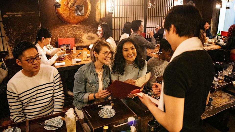 Young women ordering food in busy Japanese restaurant, fun, night out, flirting.