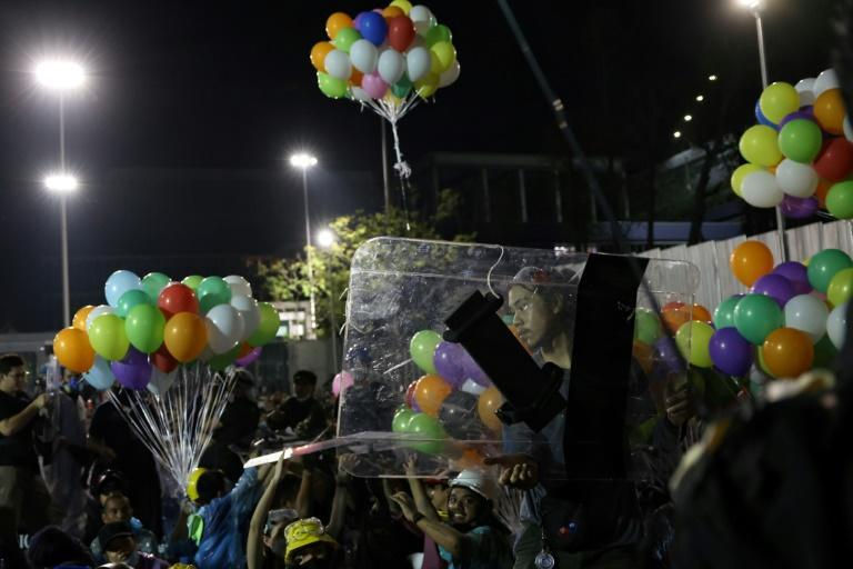 A pro-democracy protester carries a police riot shield as others hold onto colourful balloons during an anti-government rally near the Thai Parliament in Bangkok on November 17, 2020