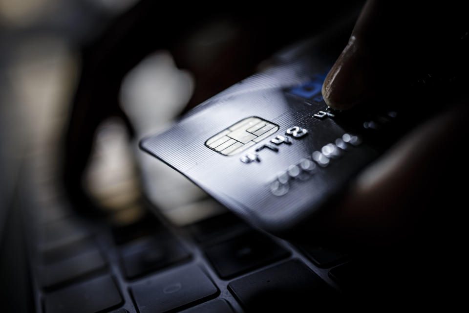 BERLIN, GERMANY - FEBRUARY 02: Symbolic photo on the subject of online shopping. A credit card is held next to the keyboard of a laptop. (Photo by Thomas Trutschel/Photothek via Getty Images)