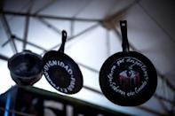 "Pots and pans used in Chile's months of anti-government demos, bearing the words: ""Now that we woke up, we must be conscious"""