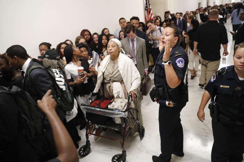 Capitol Police officer speaks to the crowd in the hallway waiting to get into hearing about reparation for the descendants of slaves at the House Judiciary Subcommittee on the Constitution, Civil Rights and Civil Liberties, at the Capitol in Washington, Wednesday, June 19, 2019. (AP Photo/Pablo Martinez Monsivais)
