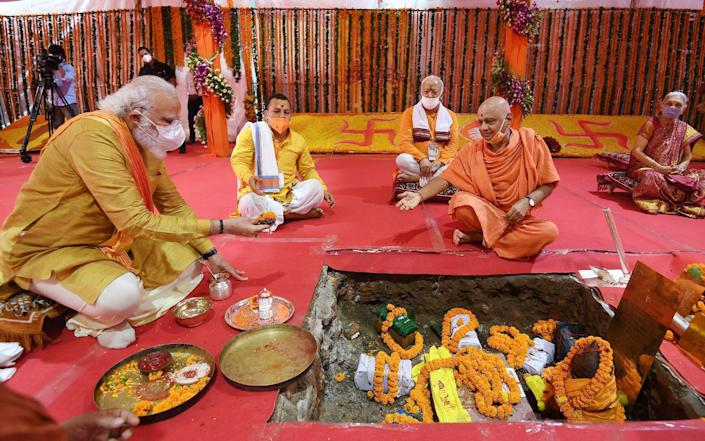 Mr Modi, left, worships at Shree Ram Janmabhoomi Mandir in Ayodhya - INDIA PRESS INFORMATION BUREAU HANDOUT/EPA-EFE/Shutterstock