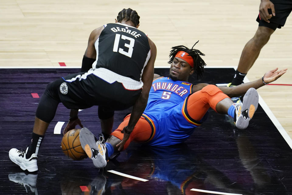 Los Angeles Clippers guard Paul George (13) picks up the ball next to Oklahoma City Thunder forward Luguentz Dort (5) during the third quarter of an NBA basketball game Friday, Jan. 22, 2021, in Los Angeles. (AP Photo/Ashley Landis)