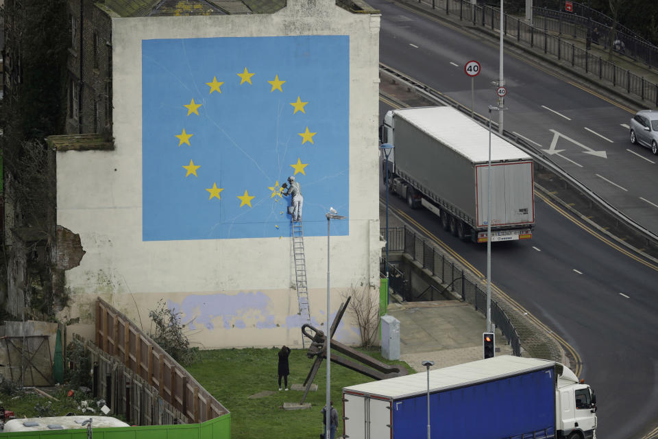 A woman takes a photograph of a mural by street artist Banksy showing a star being chiselled from the European flag in Dover, south east England, Monday, Jan. 7, 2019. Britain is testing how its motorway and ferry system would handle a no-deal Brexit by sending a stream of trucks from a regional airport to the port of Dover — even as some legislators try to pressure the government to rule out the scenario. (AP Photo/Matt Dunham)