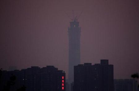 FILE PHOTO: The construction site of China Zun, planned to be the tallest building in Beijing, is seen amid smog at sunset in Beijing
