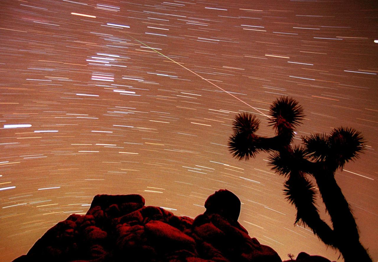 FILE - In this Nov. 17, 1998, file photo, a meteor streaks through the sky over Joshua trees and rocks at Joshua Tree National Park in Southern California's Mojave Desert in this 30-minute time exposure. The National Park Service is celebrating its 100th birthday on Thursday, Aug. 25, 2016. (AP Photo/Reed Saxon, File)
