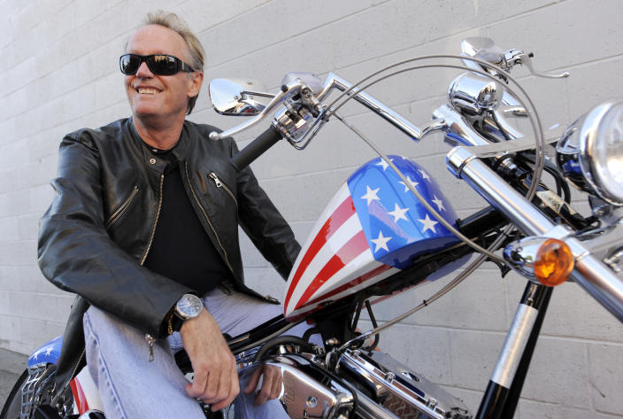 "FILE - In this Oct. 23, 2009, file photo, Peter Fonda, poses atop a Harley-Davidson motorcycle in Glendale, Calif. Fonda, the son of a Hollywood legend who became a movie star in his own right both writing and starring in counterculture classics like ""Easy Rider,"" has died. His family says in a statement that Fonda died Aug. 16, 2019, at his home in Los Angeles. He was 79. (AP Photo/Chris Pizzello, File)"