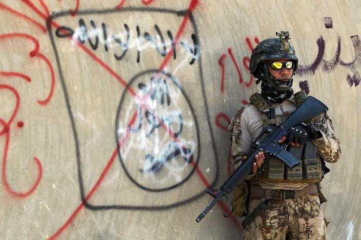 An Iraqi soldier stands next to a wall with a red cross drawn through a slogan of the Islamic State (IS) group, in Fallujah (AFP Photo/AHMAD AL-RUBAYE)