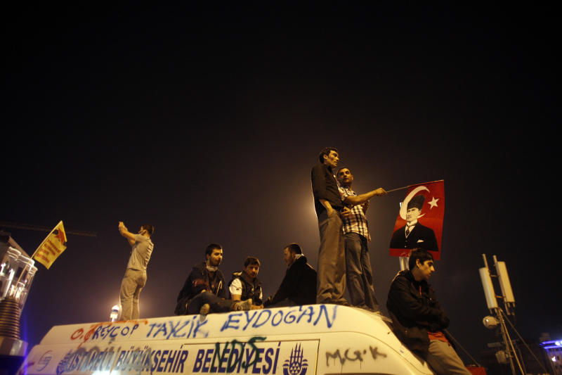 Protesters sit on top of a damaged mini bus during a protest at Taksim Square in Istanbul, Monday, June 3, 2013. Turkish riot police launched round after round of tear gas against protesters on Monday, the fourth day of violent demonstrations, as the president and the prime minister staked competing positions on the unrest. Prime Minister Recep Tayyip Erdogan rejected the protesters' demands that he resign and dismissed the demonstrations as the work of Turkey's opposition. President Abdullah Gul, for his part, praised the mostly peaceful protesters as expressing their democratic rights. (AP Photo/Kostas Tsironis)