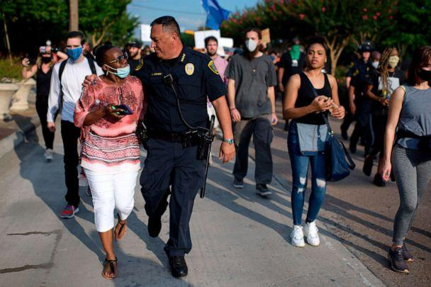 PHOTO: Houston Police Chief Art Acevedo walks arm-in-arm with a woman during a 'Justice for George Floyd' event in Houston, May 30, 2020. (Mark Felix/AFP via Getty Images)