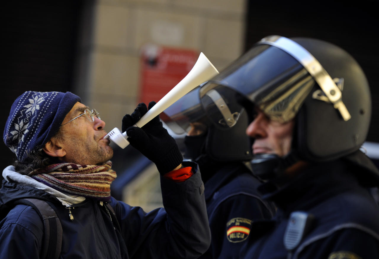 A demonstrator blows a horn in front of Spanish riot police during a general strike against government austerity measures, in Pamplona, northern Spain, Wednesday, Nov. 14, 2012. A Spanish Interior Ministry official says 32 people have been arrested and 15 people treated for minor injuries in disturbances as a general strike in Spain against austerity measures and economic reforms began. The General Workers Union said the nationwide stoppage, the second this year, was being heeded by nearly 100 percent of workers Wednesday in the automobile, energy, shipbuilding and constructions industries. (AP Photo/Alvaro Barrientos)