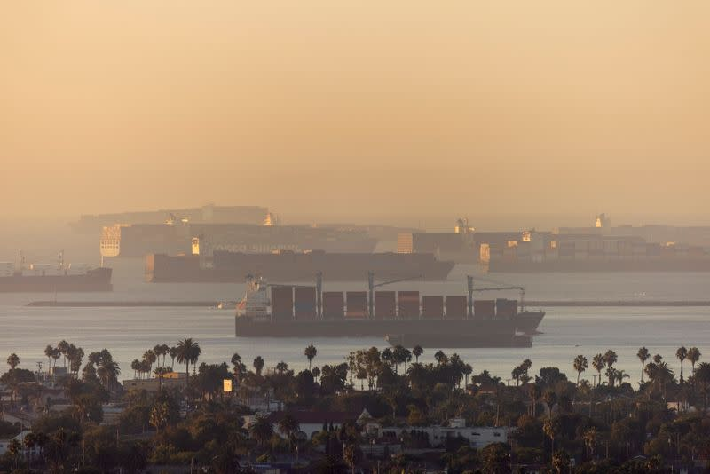 Container ships sit in the ocean waiting to unload their cargo at the ports of Los Angels and Long Beach