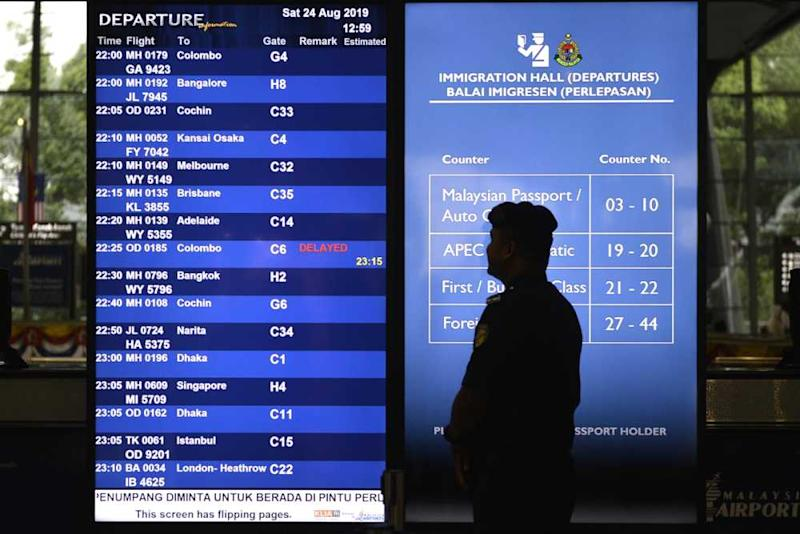 A police officer stands near the display board at the Kuala Lumpur International Airport in Sepang August 24, 2019.