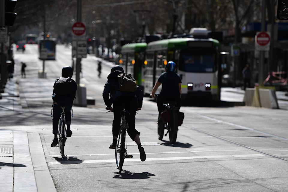 Cyclists ride up Swanston Street in Melbourne.