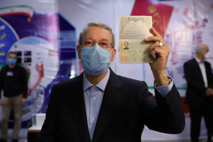 Ali Larijani, former chairman of the parliament of Iran, shows his identification document as he registers as a candidate for the presidential election at the Interior Ministry, in Tehran