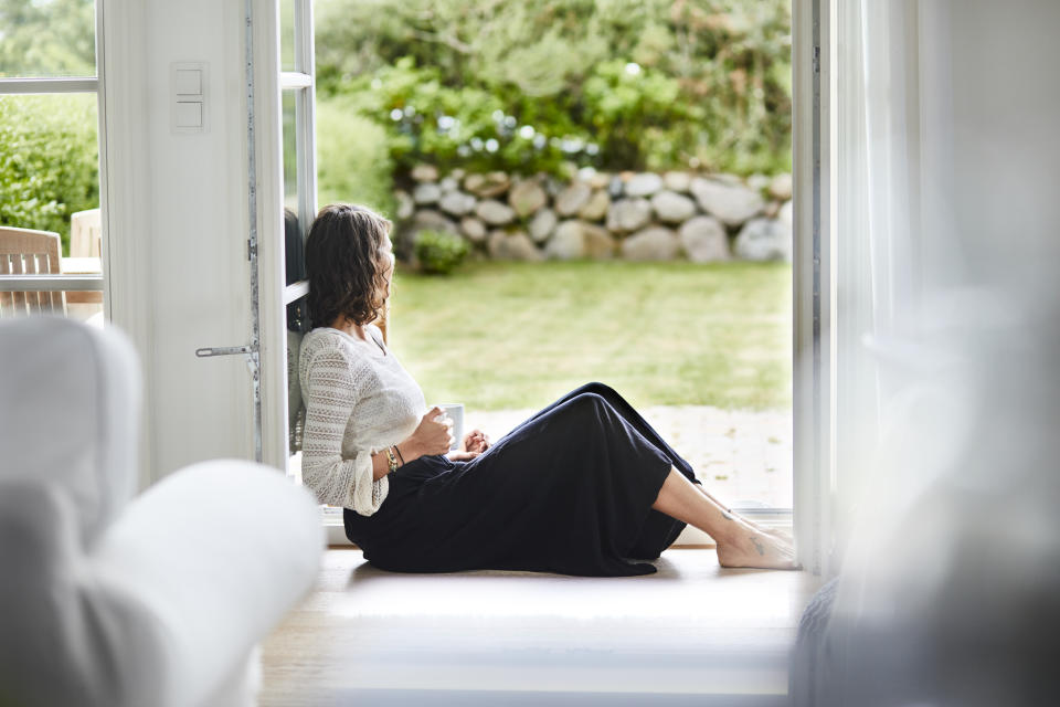 Young woman sitting in windowframe looking out