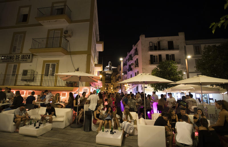 People gather at terrace bar at the port of Ibiza on July 31, 2020. - To curb the spread of coronavirus cases, the regional government of the Balearic Islands has only allowed clubs with a capacity of 300 or less to open -- and only for drinking. There cannot be a dance floor and revellers must remain seated. As a result the island's famous mega clubs, which draw big name international DJs and have made the Mediterranean island a global clubbing capital, will stay closed this season. (Photo by JAIME REINA / AFP) (Photo by JAIME REINA/AFP via Getty Images)