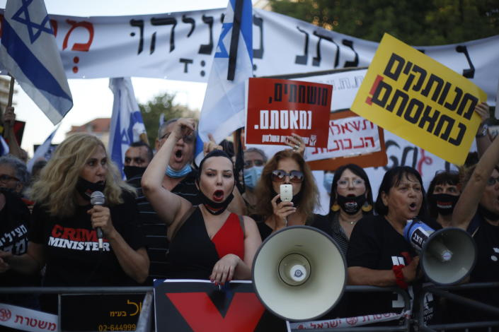 """Demonstrators, defying orders to maintain social distancing requirements, chant slogans outside of the Prime Minister's residence in Jerusalem, Tuesday, July 14, 2020. Thousands of Israelis demonstrated outside the official residence of Benjamin Netanyahu, calling on the embattled Israeli leader to resign as he faces a trial on corruption charges and grapples with a deepening coronavirus crisis. The signs read: """"You are detached. We are fed up."""" (AP Photo/Ariel Schalit)"""