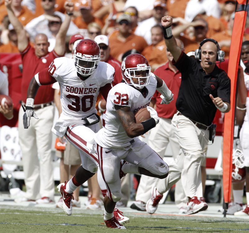Oklahoma defensive back Jamell Fleming (32) returns and interception for a touchdown followed by teammate  Javon Harris (30) during the second half of an NCAA college football game against Texas at the Cotton Bowl in Dallas, Saturday, Oct. 8, 2011. (AP Photo/Brandon Wade)