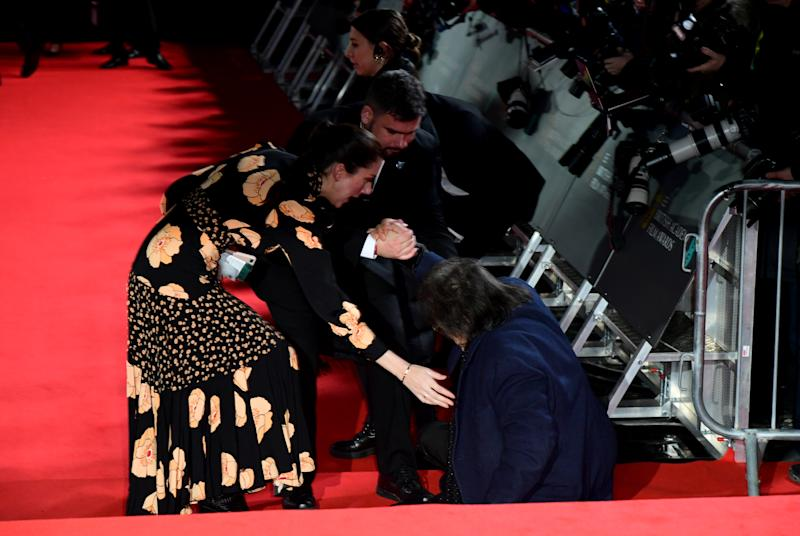 Al Pacino is helped to his feet after falling over whilst attending the BAFTA Awards at the Royal Albert Hall, London.