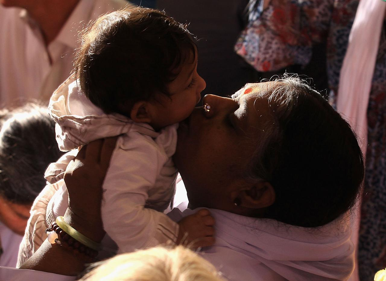 MELBOURNE, AUSTRALIA - APRIL 12:  Sri Mata Amritanandamayi Dev, known as 'Amma' (mother) hugs a visitor on the first day of her Melbourne retreat on April 12, 2012 in Melbourne, Australia. The Hindu spiritual leader is known as the 'hugging saint' by her followers and is globally respected as a humanitraian. She will be conducting retreats and a series of free public programs during her Australian tour.  (Photo by Hamish Blair/Getty Images)