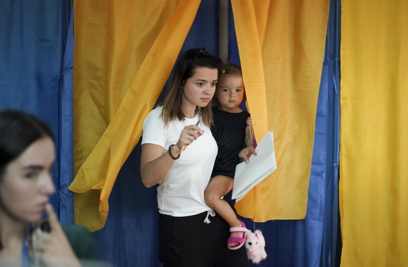 A woman with her child leaves a booth at a polling station during a parliamentary election in Kiev, Ukraine, Sunday, July 21, 2019. Ukrainians are voting in an early parliamentary election in which the new party of President Volodymyr Zelenskiy is set to take the largest share of votes. (AP Photo/Evgeniy Maloletka)