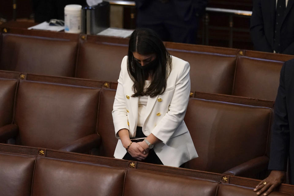 FILE - In this early Thursday, Jan 7, 2021 file photo, Rep. Alexandria Ocasio-Cortez, D-N.Y., bows her head during a closing prayer of a joint session of the House and Senate to confirm Electoral College votes at the Capitol in Washington. On Friday, Feb. 5, 2021, The Associated Press reported on stories circulating online incorrectly asserting that Ocasio-Cortez falsely claimed she faced rioters in the main Capitol building during the Jan. 6 insurrection. In a Feb. 2 Instagram Live video where the congresswomen opened up about the Capitol attack and her past sexual assault, she explained that she was in her office in a neighboring building on the Capitol complex, where she experienced a frightening encounter with a Capitol Police officer who she said didn't announce himself. (AP Photo/Andrew Harnik)
