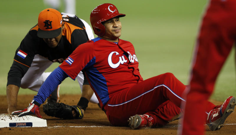 Cuba's designated hitter Frederich Cepeda is tagged out by Netherlands' first baseman Curt Smith at first base in a pickle in the second inning of their World Baseball Classic second round game at Tokyo Dome in Tokyo, Monday, March 11, 2013. (AP Photo/Koji Sasahara)