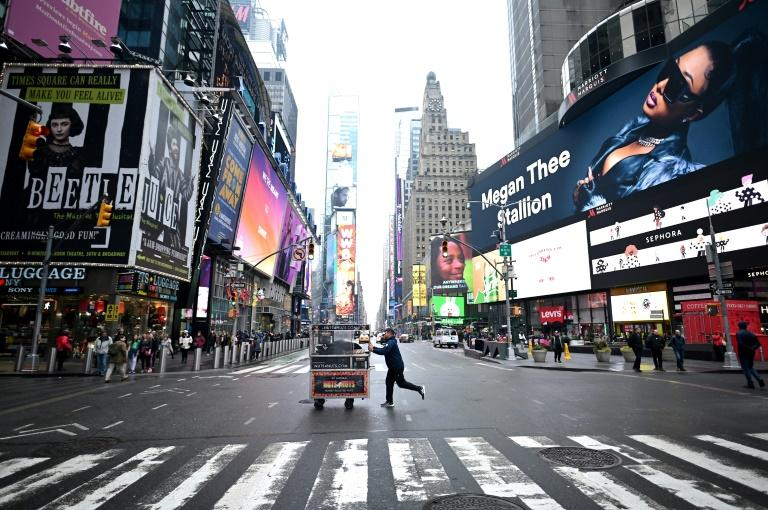 A food vendor pushes his cart across an emptier than usual Times Square on March 13 (AFP Photo/Johannes EISELE)