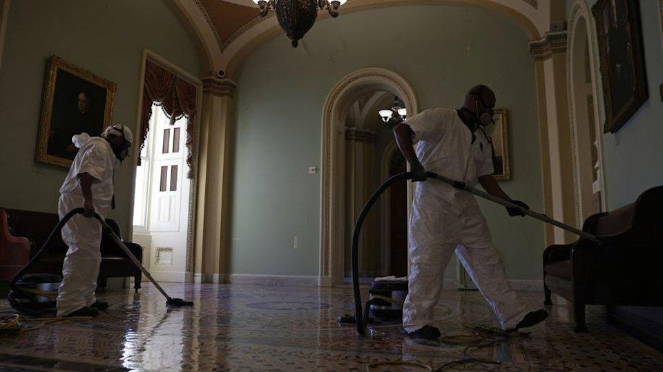 A cleaning crew vacuums the floor of a hallway at the US Capitol 7 January