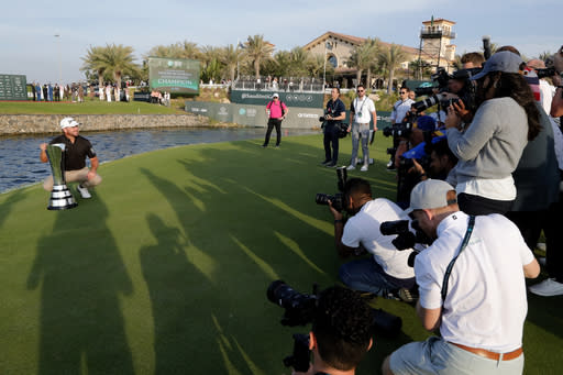 Cameramen film Graeme McDowell from Northern Ireland as he celebrates the trophy after he wins the final round of the Saudi International at Royal Greens Golf and Country Club, Sunday, Feb. 2, 2020, in Red Sea resort of King Abdullah Economic City, Saudi Arabia. (AP Photo/Amr Nabil)