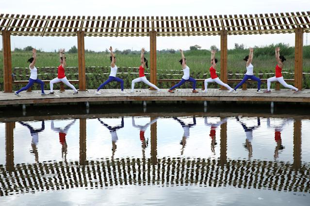 <p>Yoga enthusiasts practice yoga at a wetland park on International Yoga Day, in Zhangye, China, June 21, 2017. (Photo: Stringer/Reuters) </p>