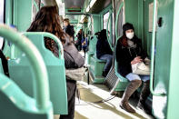 A woman wearing a sanitary mask sits in a streetcar in Milan, Italy, Monday, Feb. 24, 2020. At least 190 people in Italy's north have tested positive for the COVID-19 virus and four people have died, including an 84-year-old man who died overnight in Bergamo, the Lombardy regional government reported. (Claudio Furlan/Lapresse via AP)