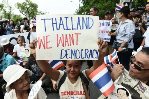 Demonstrators gather near a police barricade outside Thammasat University during a protest to mark the fourth year of junta rule in Bangkok