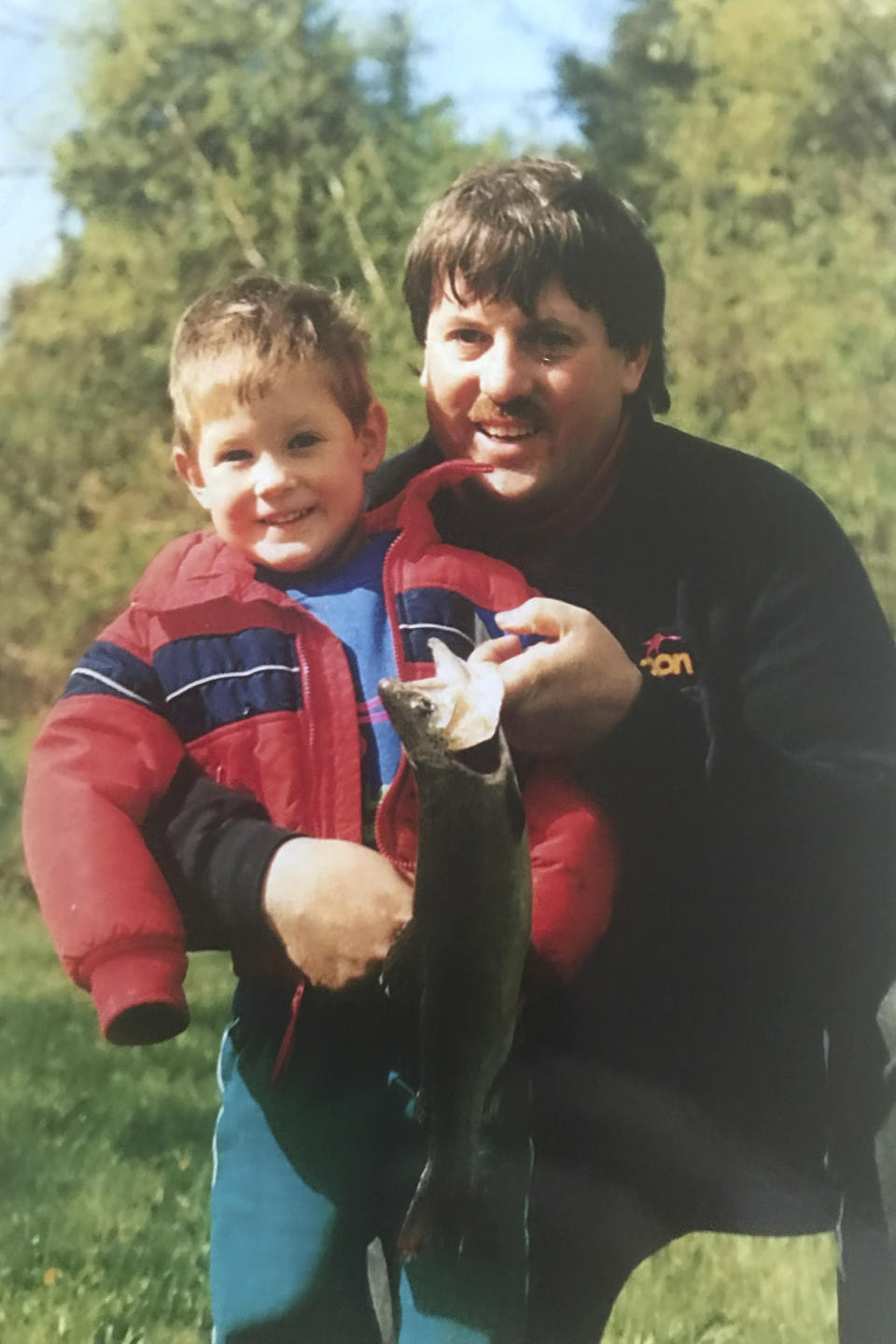 In this photo provided by Brett Eagleson, Sept. 11 victim Bruce Eagleson holds his son Brett and a fish they caught together at a fishing derby in New Hampshire in 1993. Eagleson and others who have lost family on Sept 11 are seeking the release of FBI documents that allege Saudi Arabia's role in the terrorist attacks. A lawsuit that accuses Saudi Arabia of being complicit took a major step forward this year with the questioning under oath of former Saudi officials, but those depositions remain under seal and the U.S. has withheld a trove of other documents as too sensitive for disclosure. (Brett Eagleson via AP)