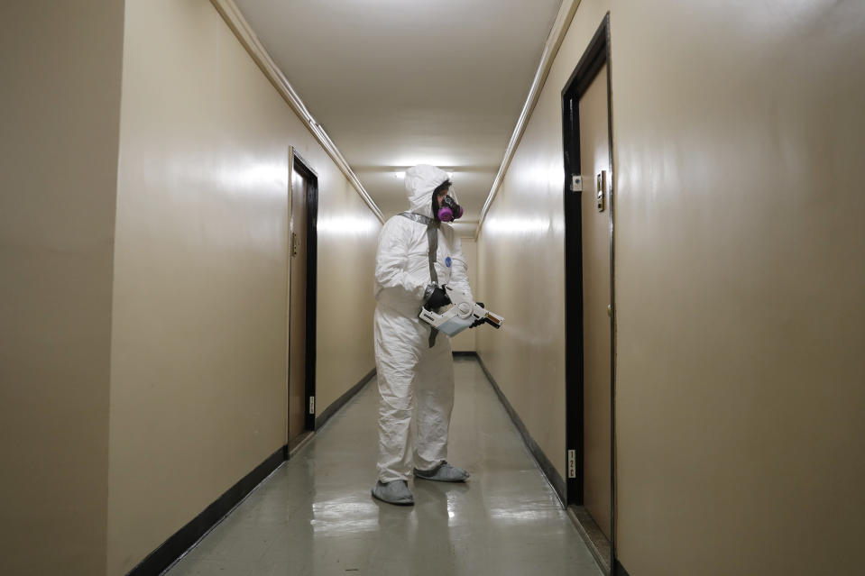 Safety Director Tony Barzelatto sprays disinfectant in a hallway of a building in Co-op City in the Bronx borough of New York, Wednesday, May 13, 2020. Regular cleanings occur throughout the common areas of the buildings while the heavy disinfecting occurs in response to specific incidents, in this case reports of two coronavirus cases on the same floor. Within the Bronx, almost no place has been hit as hard as Co-op City. (AP Photo/Seth Wenig)