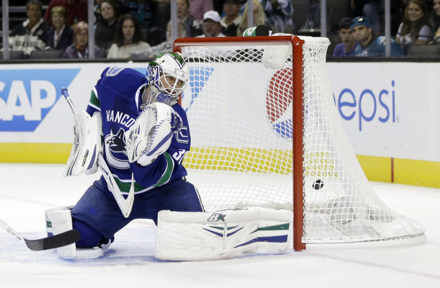 Vancouver Canucks goalie Eddie Lack is beaten for a goal on a shot from San Jose Sharks defenseman Dan Boyle during the first period of a preseason NHL hockey game on Tuesday, Sept. 24, 2013, in San Jose, Calif. (AP Photo/Marcio Jose Sanchez)