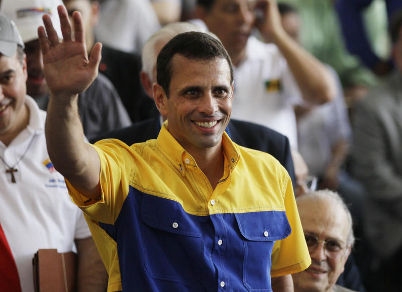 Opposition presidential candidate Henrique Capriles waves during a ceremony to register his candidacy for the presidency in Caracas, Venezuela, Sunday, June 10, 2012. Capriles will face Venezuela's President Hugo Chavez in the presidential elections scheduled for Oct. 7. (AP Photo/Ariana Cubillos)
