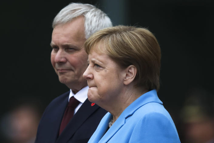 German Chancellor Angela Merkel and Prime Minister of Finland Antti Rinne listen to the national anthems during the welcoming ceremony at the chancellery in Berlin, Germany, Wednesday, July 10, 2019. (AP Photo/Markus Schreiber)