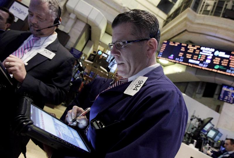 Traders Robert Moran, left, and Sean Spain work on the floor of the New York Stock Exchange Thursday, Dec. 6, 2012. Stocks are opening mixed on Wall Street following news that Europe will hold off on new economic stimulus measures. (AP Photo/Richard Drew)