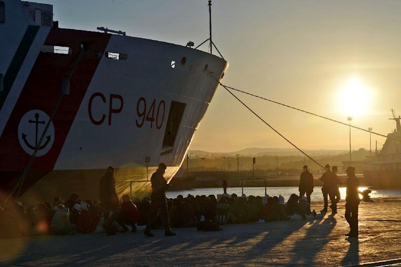 Shipwrecked migrants sit on the quay after disembarking from a rescue vessel in the Italian port of Augusta in Sicily on April 16, 2015 (AFP Photo/Giovanni Isolino)