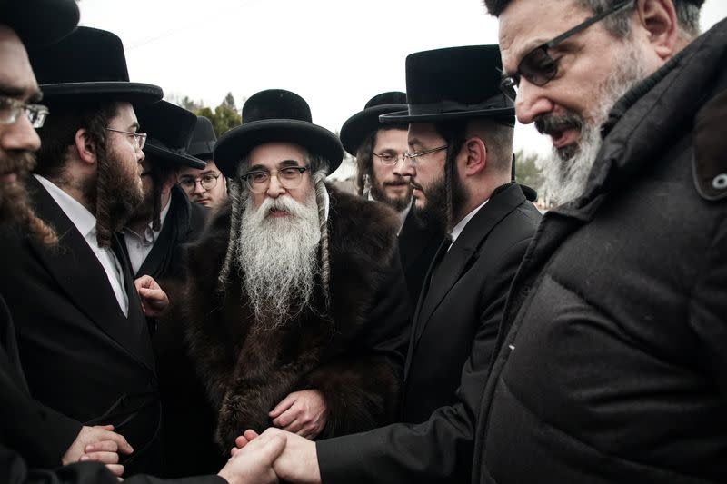 Rabbi Chaim Rottenberg shakes a hand with people in Monsey
