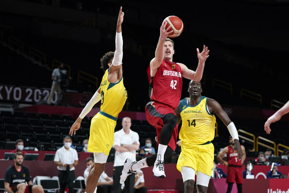 Germany's Andreas Obst (42) drives to the basket between Australia's Matisse Thybulle (10) and Duop Reath (14) during a men's basketball preliminary round game at the 2020 Summer Olympics, Saturday, July 31, 2021, in Saitama, Japan. (AP Photo/Charlie Neibergall)