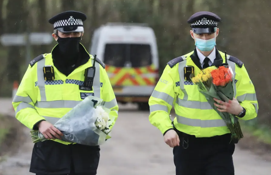 Police officers carry flowers from members of the public at Great Chart Golf and Leisure near Ashford in Kent following the discovery of human remains. (PA)