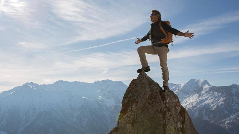 A male mountain climber standing on a peak.