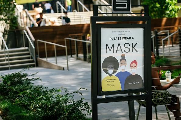 A sign reads 'Please Wear A Mask' displayed at a plaza in Atlanta, Georgia, USA.