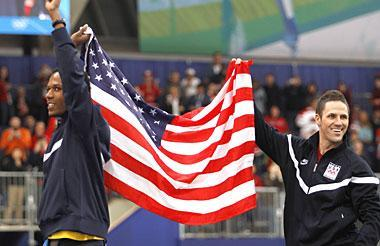Gold medallist USA's Shani Davis, left, and Bronze medallist USA's Chad Hedrick, right, walk to the podium of the flower ceremony